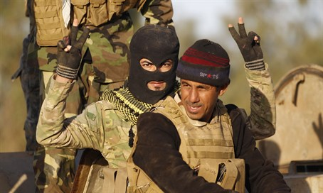 Shia militiamen gesture during clashes with ISIS in Iraq