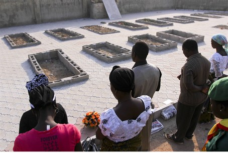 People pray near the graves of victims of an