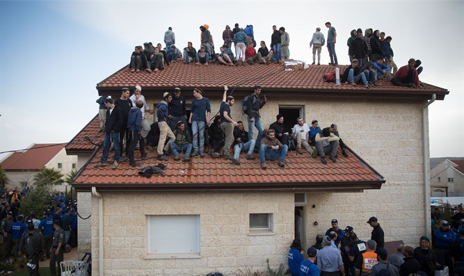 Protesters on the roof of an Ofra home